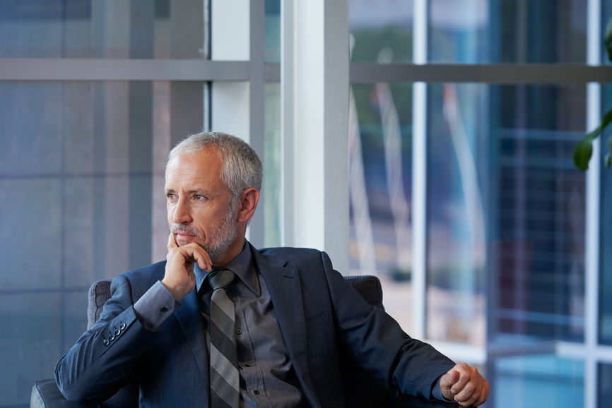 Businessman in suit staring out office window
