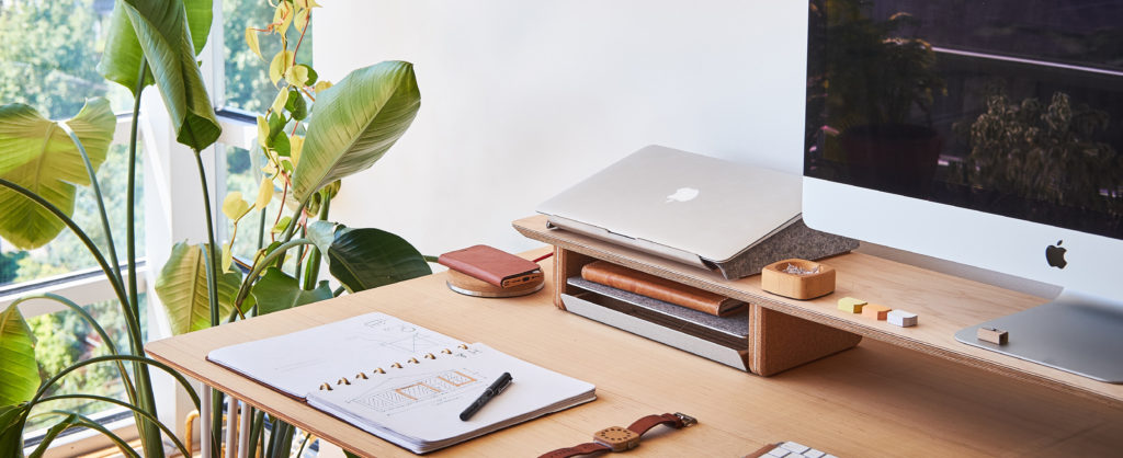 Desk with computer monitor, laptop, and planner on top of it with a plant next to it.